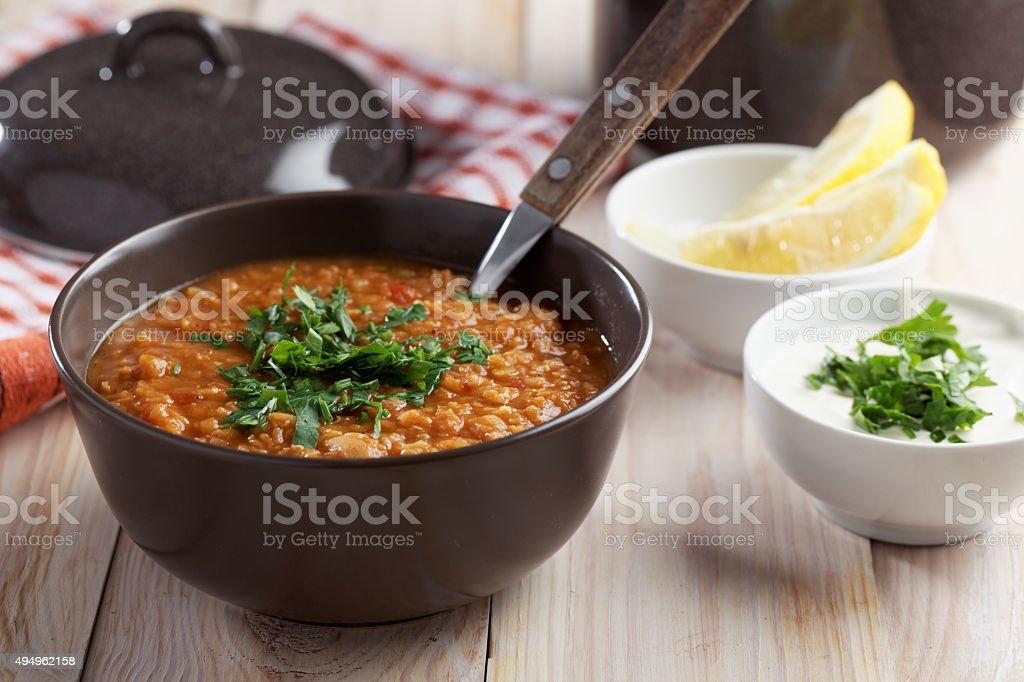 Red lentil soup and Greek yogurt Red lentil soup and Greek yogurt with parsley on a rustic table 2015 Stock Photo