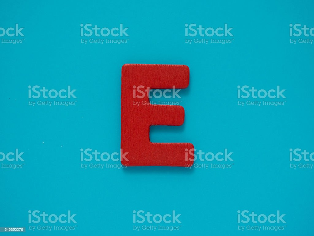 Red letter E from wood on blue background. Alphabet vowel. stock photo