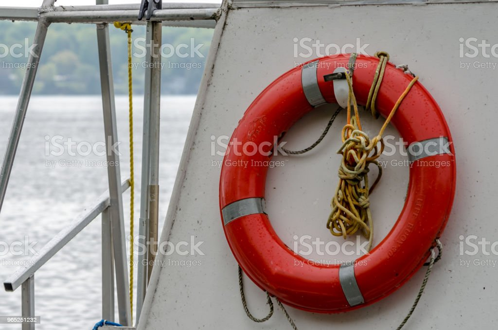 Red life preserver mounted on a boat with water and shoreline in the background. royalty-free stock photo