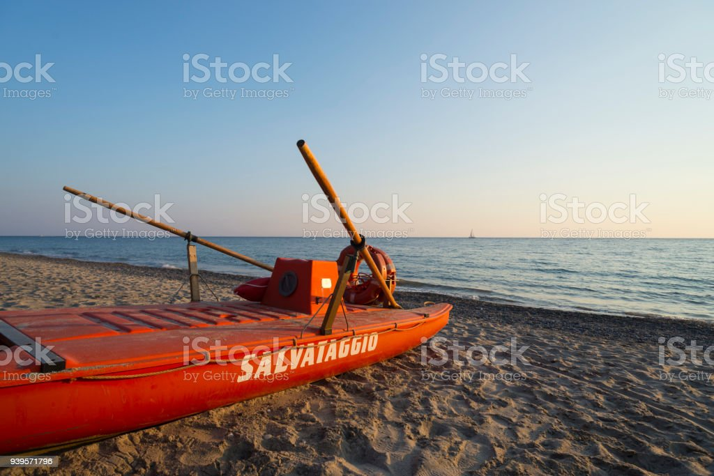 Red lifeboat  at sunset on the Mingardo beach at the Mediterranean Sea near Palinuro in the Cilento region in southern Italy stock photo
