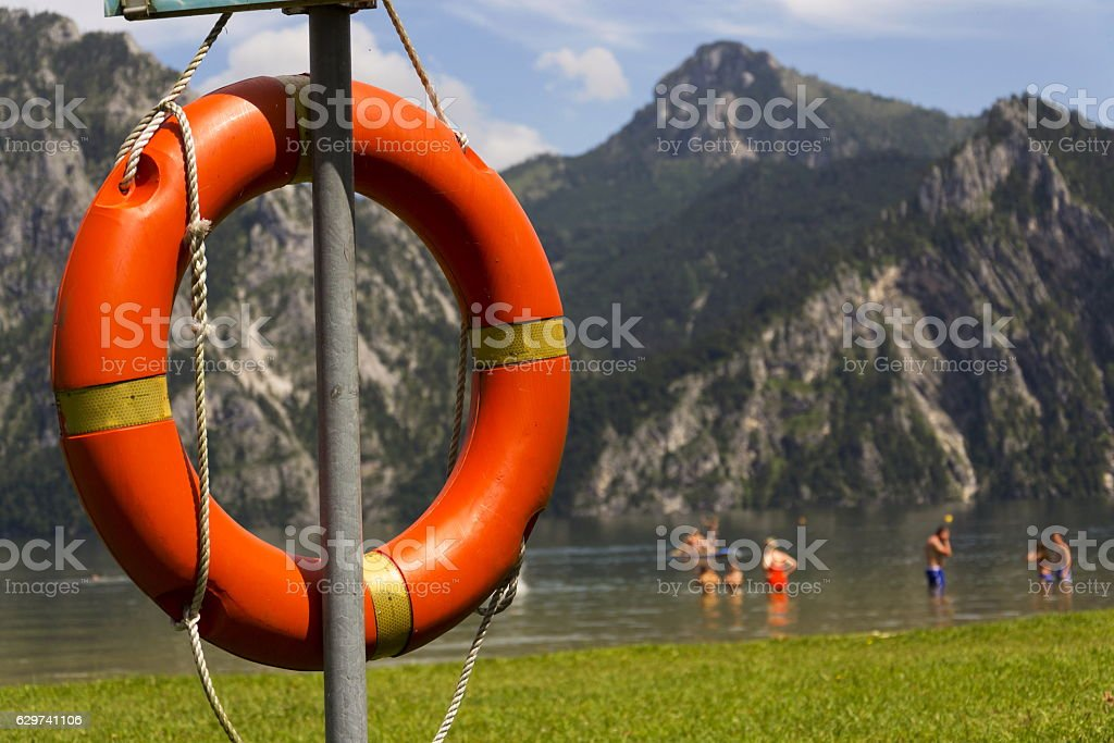 Red lifebuoy hang by mountain lake Traunsee, Salzkammergut Upper Austria stock photo