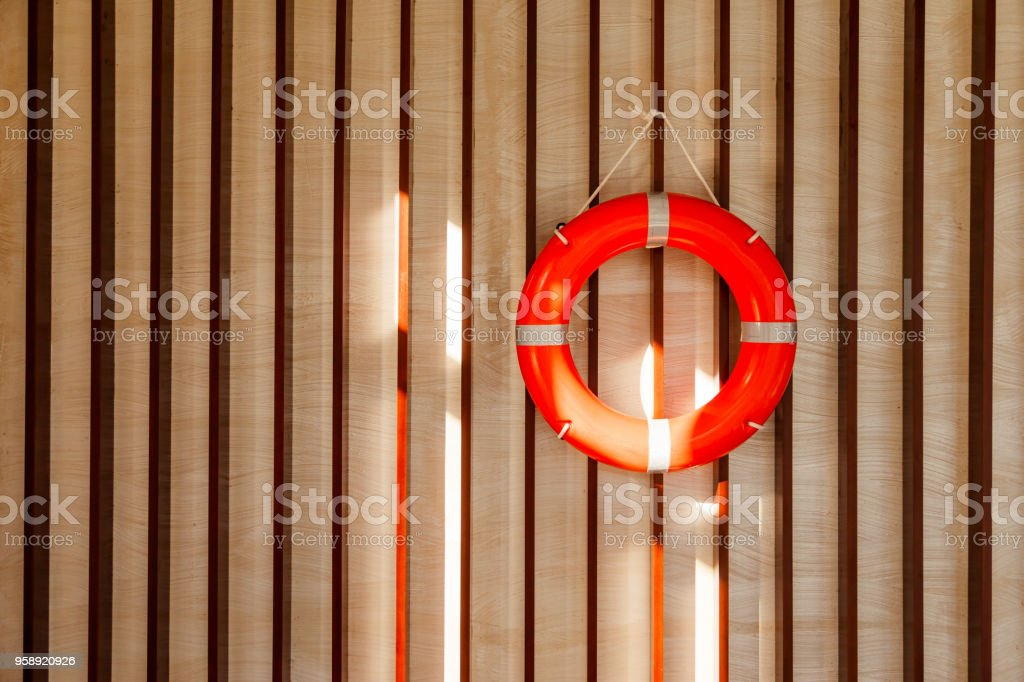 Red lifebuoy hanging on blue wooden wall of a port building stock photo