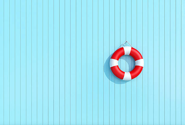 Red lifebuoy in a old grunge wooden plank wall of blue stock photo