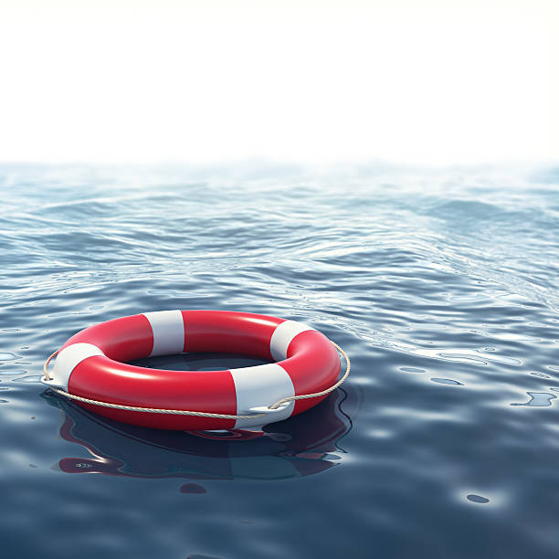 Red lifebuoy in blue sea with depth of field effect stock photo