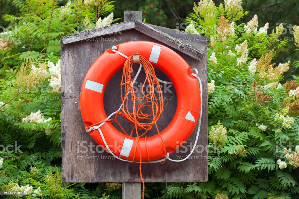 Red lifebuoy with ropes hanging in wooden box stock photo