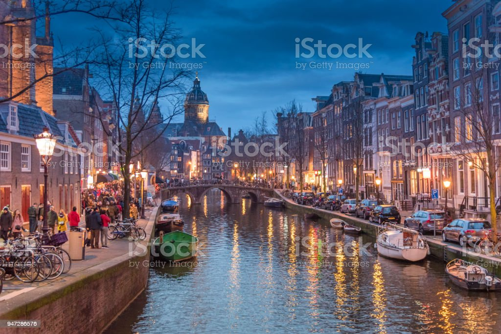 Red light destrict view and Amsterdam canal, bicycles and cyclists, houseboats, living boats. (ED) stock photo