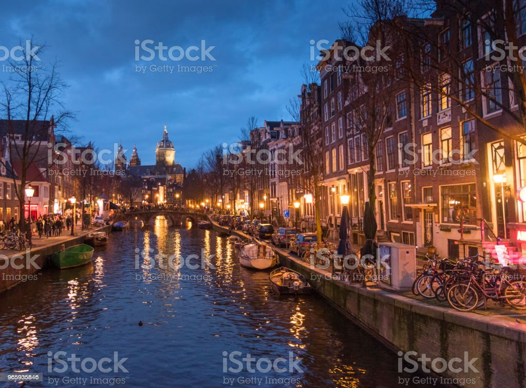 Red light destrict view and Amsterdam canal, bicycles and cyclists, houseboats, living boats. - Royalty-free Amsterdam Stock Photo