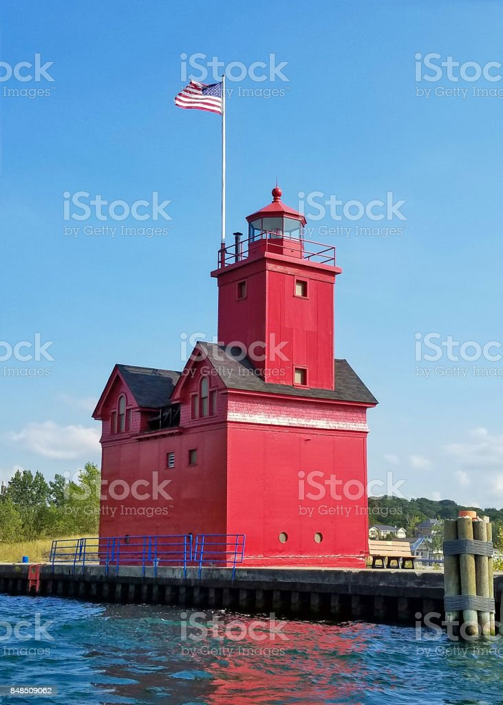 red lighthouse in Michigan harbor stock photo