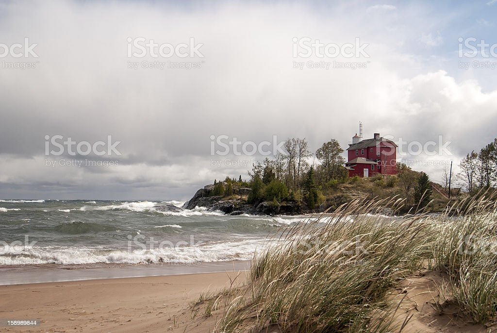 Red lighthouse located in lower harbor on a stormy day stock photo