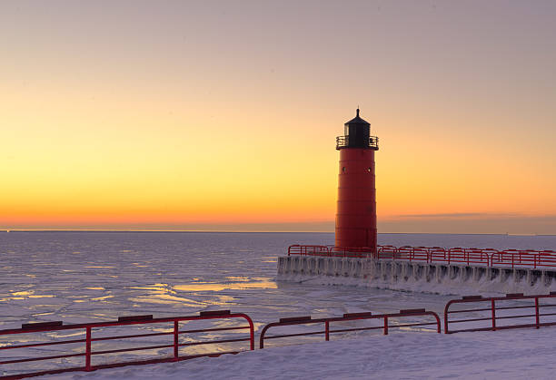 Red lighthouse on Lake Michigan in Winter at sunrise Red lighthouse taken at sunrise on Lake Michigan in the winter with icy water and colorful sky. milwaukee wisconsin stock pictures, royalty-free photos & images