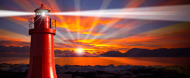 Red Lighthouse with Light Beam at Sunset Red and metallic lighthouse with light beam at sunset with clouds beacon stock pictures, royalty-free photos & images