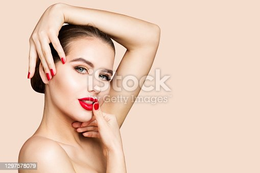 Red Lips and Nails Model Portrait, Woman Beauty Make Up, Red Lipstick. Skin Care Cosmetology. Beautiful Girl Face Makeup. Beige Background