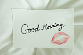 Red lips kiss Good morning on white note message on bed