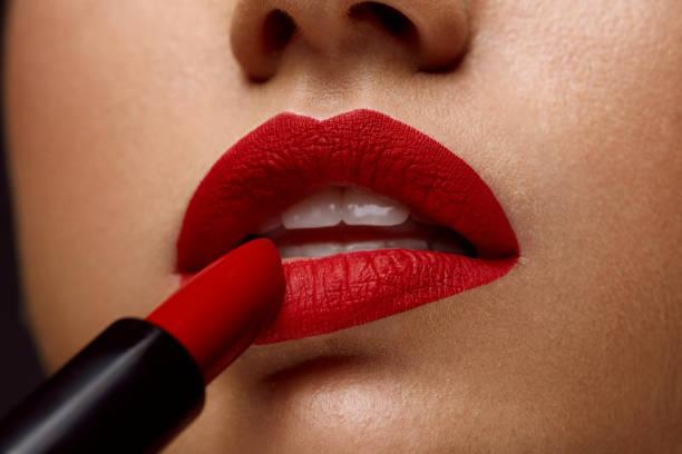 lápiz de labios rojo. primer plano del rostro de la mujer con el maquillaje de labios brillante - labios rojos fotografías e imágenes de stock