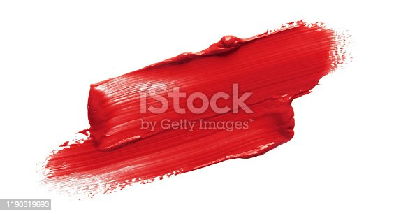 Red lipstick smear smudge swatch isolated on white background. Makeup texture. Red color cream brush stroke swipe sample. Cosmetic product macrophotography