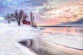 A winter photo of a red little cottage with some trees in the archipelago of Stockholm, Sweden. There is snow on the ground and some ice on the lake. The sky is colored from the beautful winter sunset.