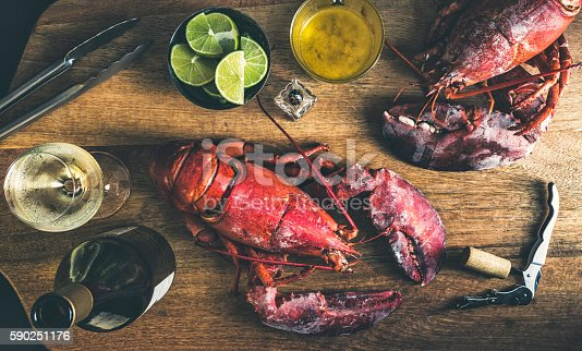 Directly above view of a wood table with two red and fresh lobsters ready to eat, accompanied by white wine lemon and butter. The picture is an studio shot with a combination of natural and artificial light to achieve a very intimate ambiance.