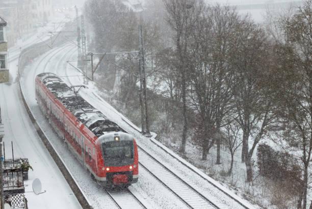 roten nahverkehrszug in einem schneefall in der stadt schweinfurt - deutsche wetter stock-fotos und bilder