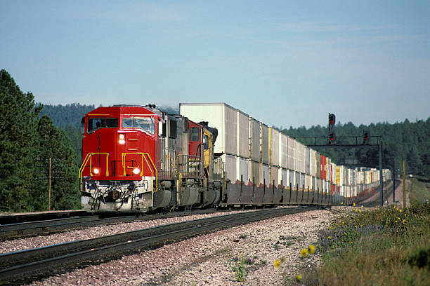red locomotive and double stack freight train - godståg bildbanksfoton och bilder