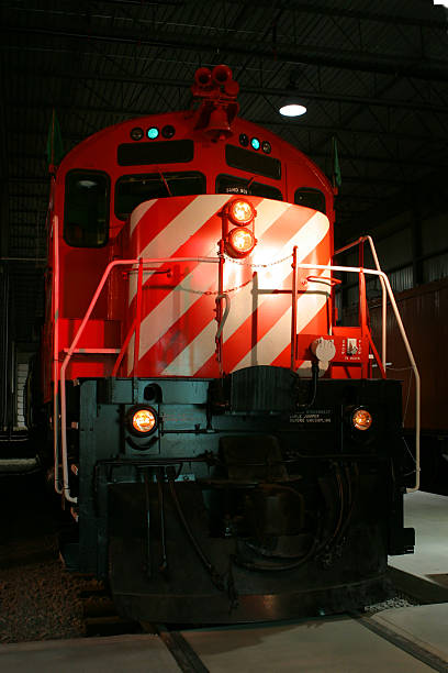 Red locomotive inside a station maintenance building stock photo