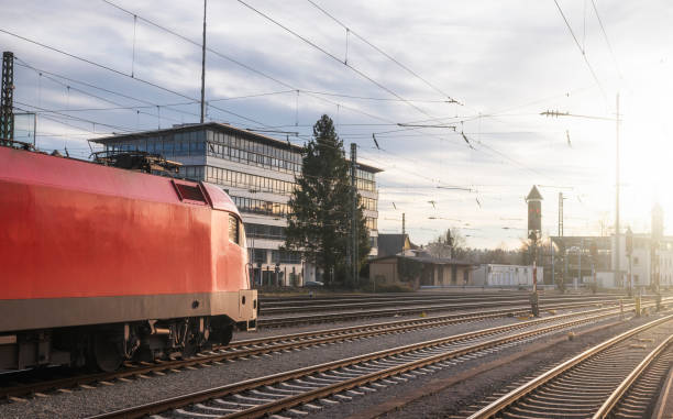 Red locomotive on railroad tracks at sunset. Train transport context Modern red locomotive traveling on railway tracks. Public transport. Train travel concept. High-speed locomotive near Singen train station, Germany. singen stock pictures, royalty-free photos & images