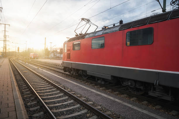 Red locomotive on railway tracks in german train station at sunset Electric locomotive on railroad tracks in Singern train station, Germany, at sunset. Eco-friendly public transport. Red locomotive on tracks. singen stock pictures, royalty-free photos & images