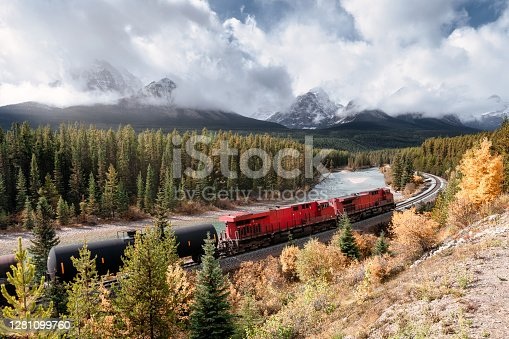 Red long freight train on railway passing through autumn valley with mountain at Morant's Curve, Calgary, Canada