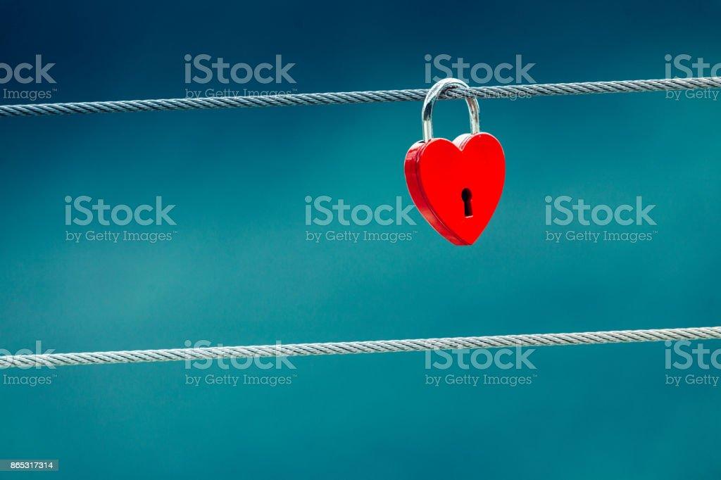 Red love lock padlock on bridge outdoor stock photo