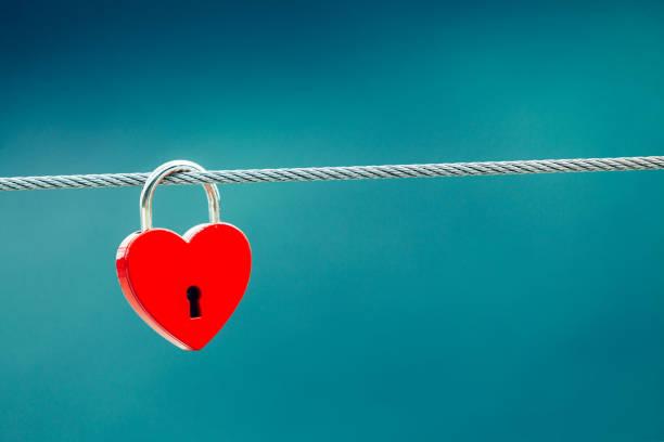 red love lock padlock on bridge outdoor - fedeltà foto e immagini stock