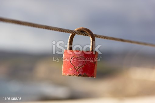 Rusty lock with heart shape carved hanging on railing outdoors. Valentines day, unity, memory concepts