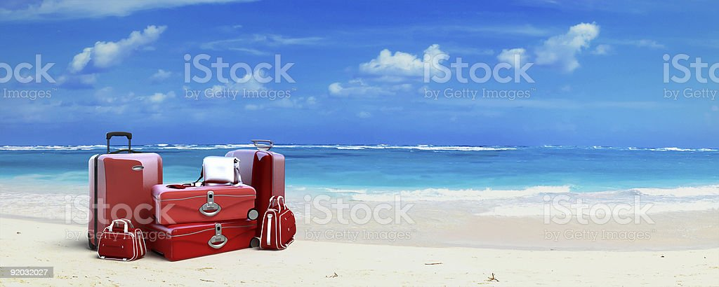 Red Luggage at the beach stock photo