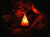 Glowing red Christmas toy hanging on the tree in the dark and illuminates around itself