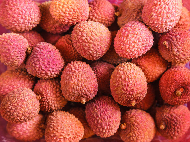 red lychee a lot of ripe juicy red lychee close up spiked stock pictures, royalty-free photos & images