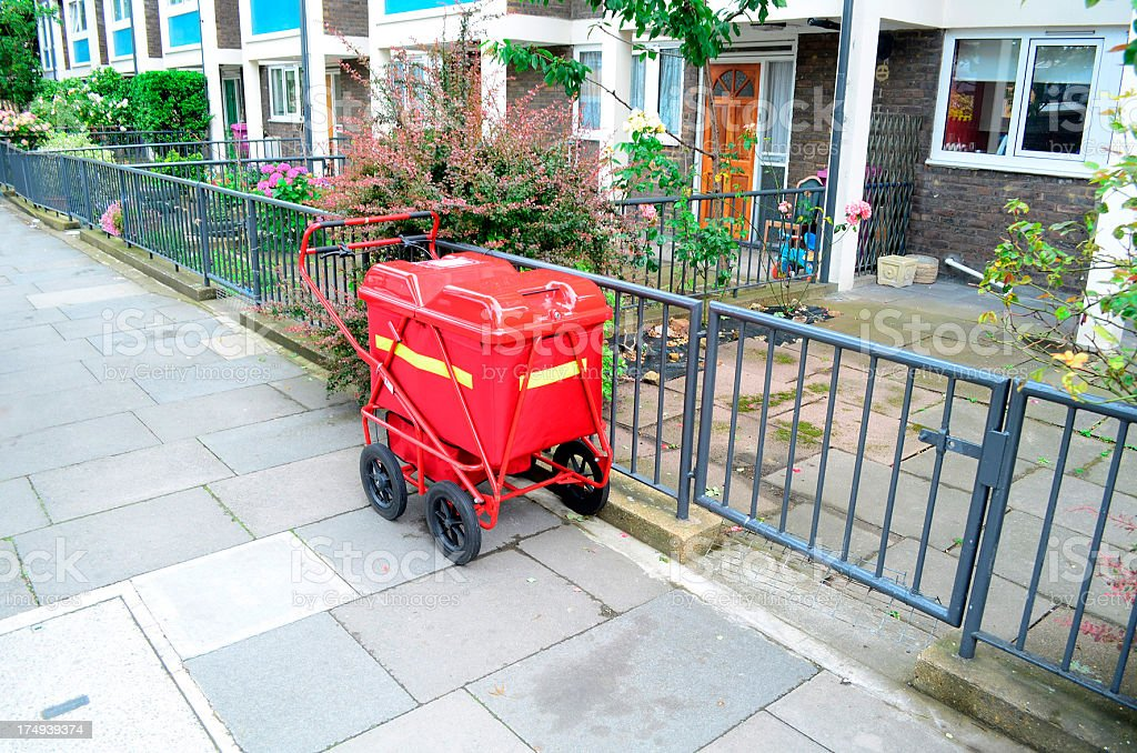 red mail buggy on sidewalk in London neighborhood royalty-free stock photo
