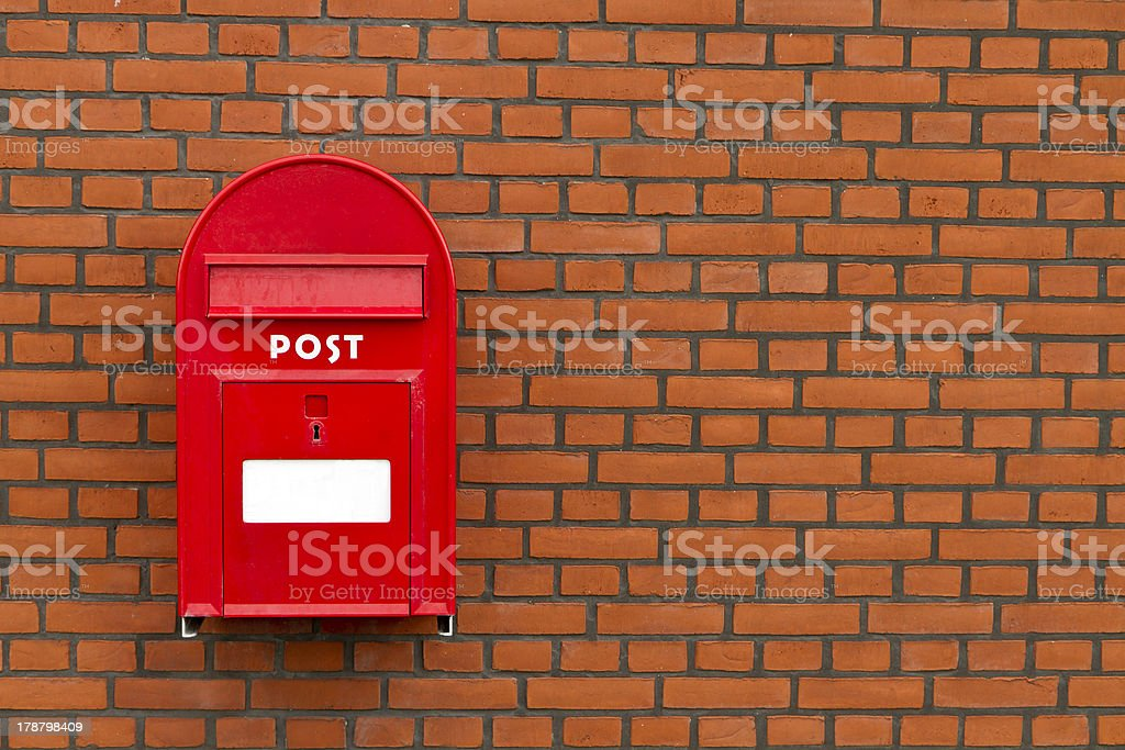 red mailbox on stone wall stock photo