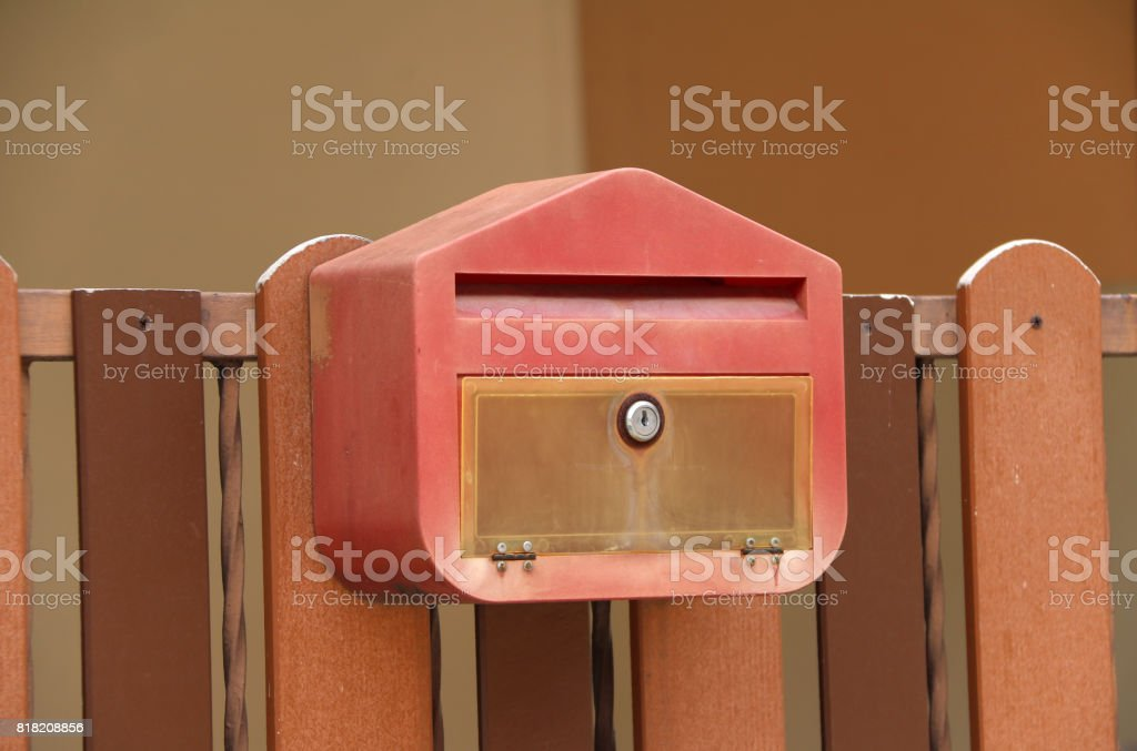 Red mailbox with brown wood fence. stock photo