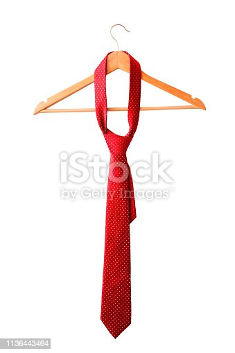 Red male tie hanging on the wooden rack. Isolated on white background.