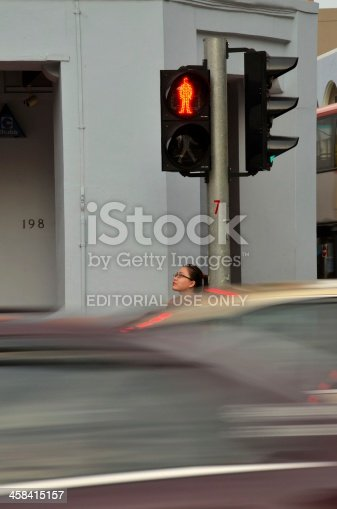 Singapore - January 12, 2013: A woman stares upwards towards the sky while waiting for a 'Red Man' signal to change at a pedestrian crossing in Singapore. The outlines of blurred cars in motion are visible in the foreground of the photo.