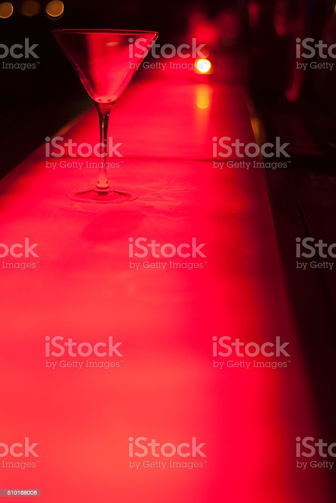 Red martini glass on bar stock photo