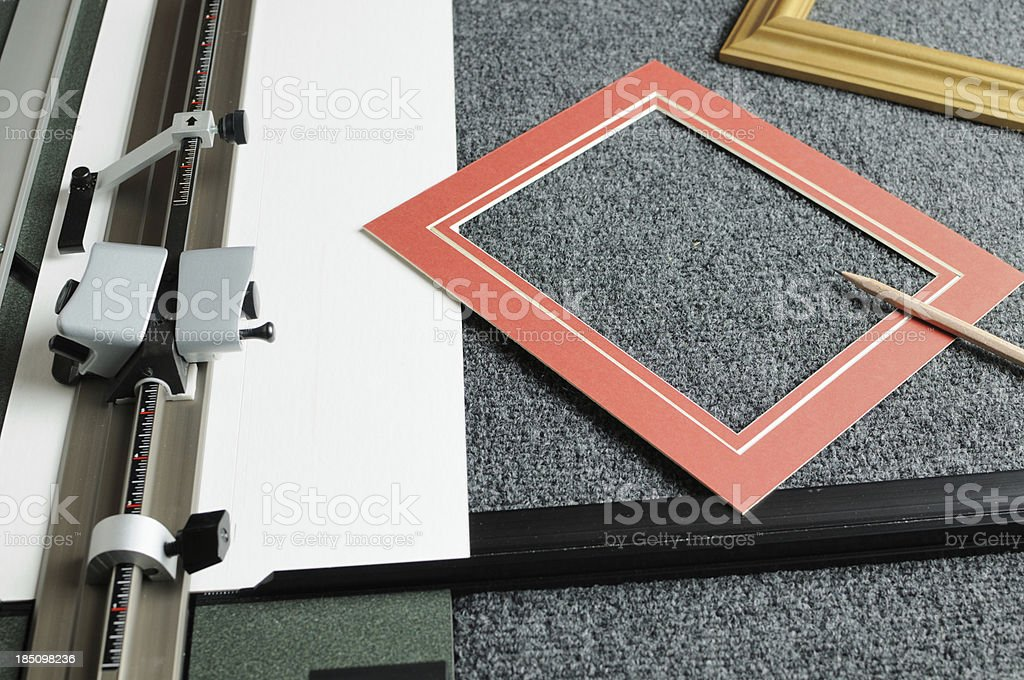 red mat board and picture frame near cutter royaltyfree stock photo
