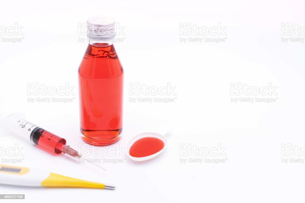 Red medical syrup , syringe of injection and yellow thermometer on white background. stock photo