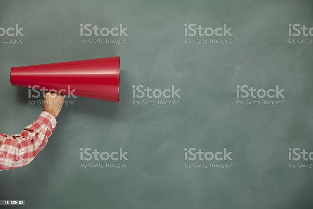 Red Megaphone In Human Hand On Green Blank Blackboard stock photo