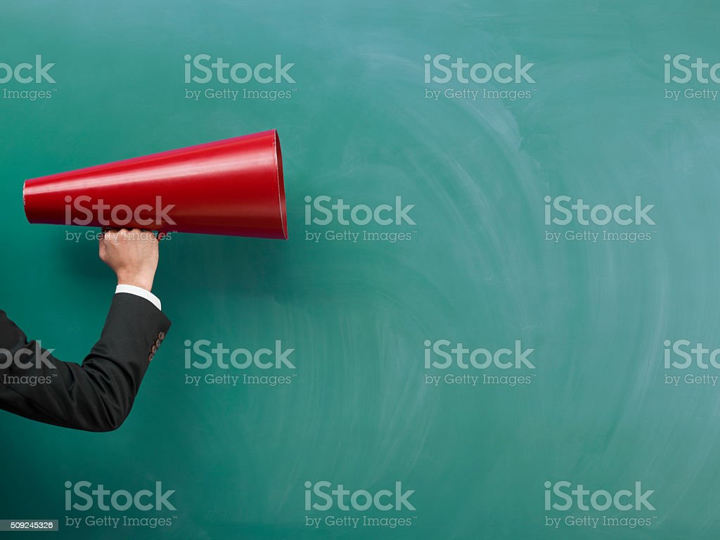 Red Megaphone In Human Hand On Green Blank Blackboard stock photo