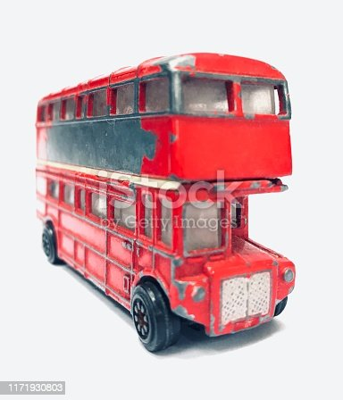 Red metal model of an old London Route Master bus. An old toy with flaking red paint.