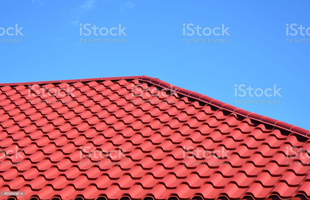 Red metal tiled roof house roofing construction exterior. stock photo