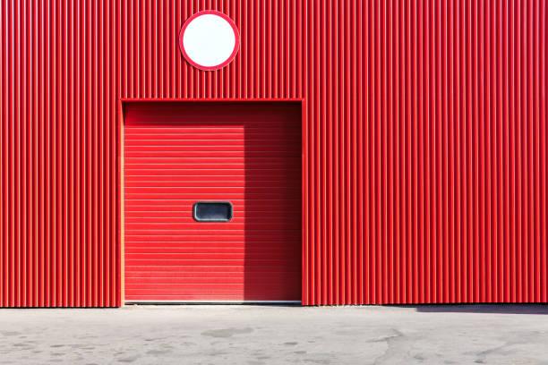rot metall-lagerhalle wand mit geschlossenen rollladen rolltor - garagentor mit tür stock-fotos und bilder