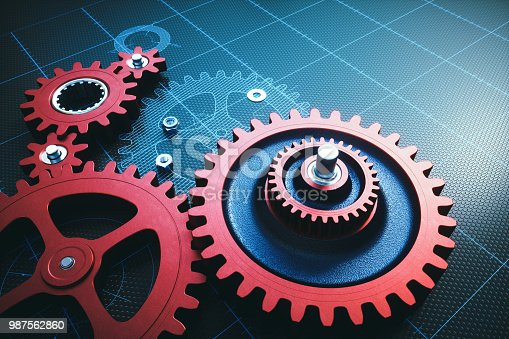 istock Red metallic gears on a grid with hatched schematics 987562860