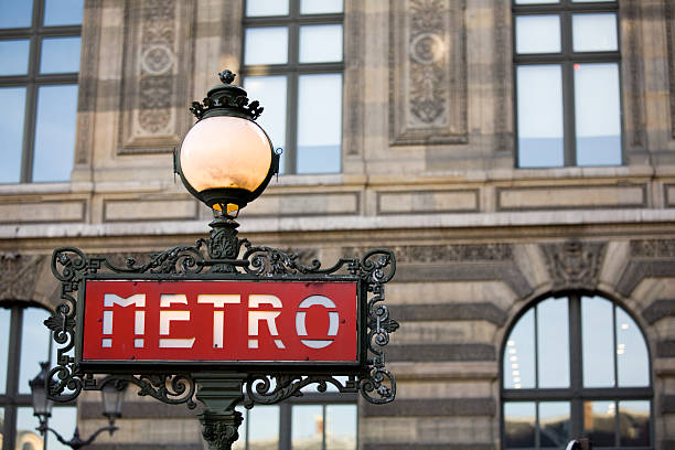 Red metro sign with light in Paris, France The Paris Metro sign shown against the Louvre museum as background.     Check out my  musee du louvre stock pictures, royalty-free photos & images