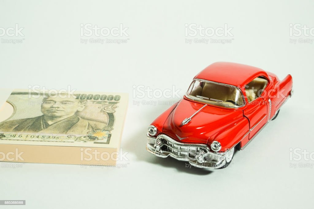 Red miniature classic car and Japanese money. white background stock photo