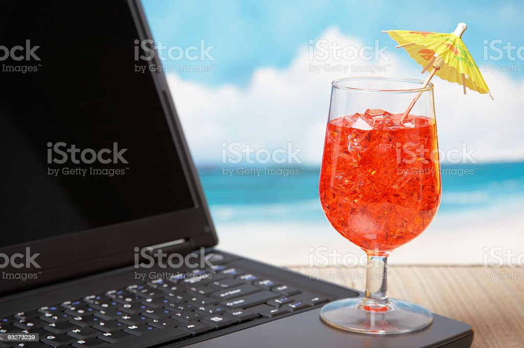 Red mixed drink yellow umbrella sitting on open laptop beach royalty-free stock photo